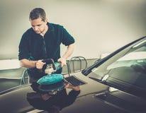 Worker on a car wash. Man on a car wash polishing car with a polish machine Royalty Free Stock Photos