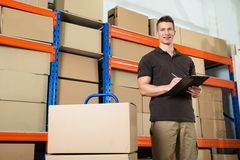 Worker With Cardboard Boxes Writing On Clipboard. Male Worker With Cardboard Boxes Writing On Clipboard In Warehouse Royalty Free Stock Photo