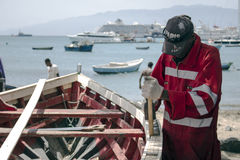 Worker carpenter repairing a wooden boat. A black man is fixing a wooden boat at the beach in Cape Verde Stock Photos