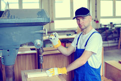 Worker in a carpenter's workshop using drilling machine stock photo