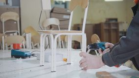 Worker carpenter is screwing chair leg at a furniture factory. Industry concept Royalty Free Stock Photo