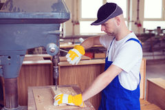 Worker in a carpenter's workshop using drilling machine Royalty Free Stock Image