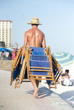 Worker carries deckchairs to put them away at the end of the day. Man with a tan and no shirt wearing a straw hat carries beach chairs on the boardwalk Stock Photo