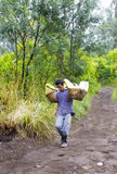 Worker carries sulfur from crater Royalty Free Stock Photos