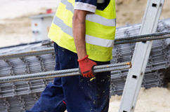 Worker carrying armature Royalty Free Stock Photos