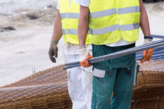 Worker carrying armature Stock Image