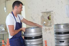 Worker carrying barrel with beer at brewery. Worker carrying barrel with beer at the brewery Royalty Free Stock Image