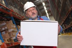 Worker carrying box. Older worker in uniform and hardhat carrying box in warehouse Royalty Free Stock Images