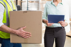 Worker carrying box with manager holding tablet pc Royalty Free Stock Image