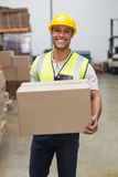 Worker carrying box in warehouse Stock Image