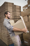 Worker carrying box in warehouse Stock Photography