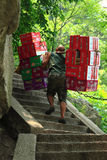 Worker is carrying boxes with beverages. Mountain Huangshan, China - June 17, 2013: worker is carrying boxes with beverages to the top of the Mountain Huangshan Stock Photo