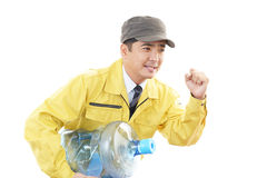 Worker carrying large water bottle. Stock Images