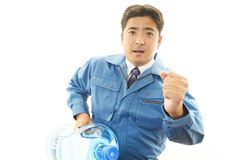 Worker carrying large water bottle. royalty free stock photography