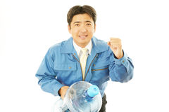 Worker carrying large water bottle. royalty free stock image