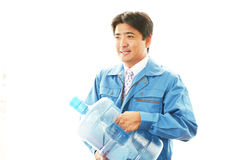 Worker carrying large water bottle. stock photography