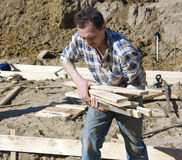 Worker carrying planks Royalty Free Stock Image