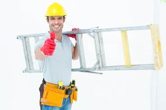Worker carrying step ladder while showing thumbs up Royalty Free Stock Photo