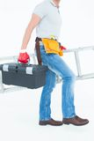 Worker carrying step ladder and tool box Stock Photo
