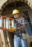 Worker Carrying Stepladder. At construction site Royalty Free Stock Photography