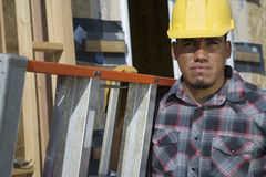 Worker Carrying A Stepladder. Portrait of a male architect carrying stepladder at construction site Stock Image