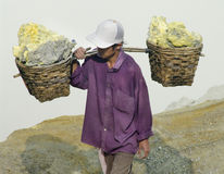 Worker carrying sulfur inside Ijen crater Stock Photo