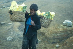 Worker carrying sulfur inside Ijen crater. Stock Photo