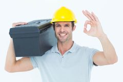 Worker carrying tool box on shoulder while gesturing OK sign. Portrait of happy worker carrying tool box on shoulder while gesturing OK sign over white Stock Photos