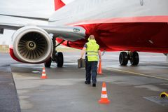 Worker Carrying Traffic Cone And Chocks By Airplane On Runway. Rear view of male worker carrying traffic cone and chocks by airplane on wet runway royalty free stock images