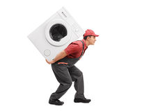 Worker carrying a washing machine on his back Stock Photography
