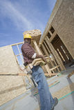 Worker Carrying Wooden Beam At Site Stock Photos