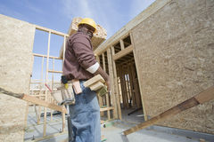 Worker Carrying Wooden Beam At Site Stock Image