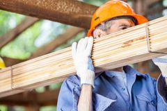 Worker Carrying Wooden Planks At Construction Site Stock Photography