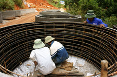 Worker casting cement culvert for road-works Royalty Free Stock Photography
