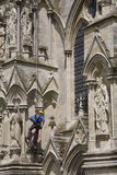 Worker on Cathedral Exterior. A worker, dangling from a rope on the exterior of Salisbury Cathedral in England, cleaning, repairing or restoring the carved stone Royalty Free Stock Photos