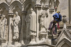 Worker on Cathedral Exterior. Man suspended on rope, working on the stone facade of the Gothic-style cathedral at Salisbury in England Royalty Free Stock Photography