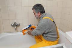 Worker caulking bath tube and tiles Stock Photography