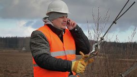 Worker with cell phone and adjustable wrench on field stock video