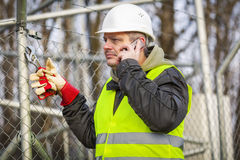 Worker with cell phone and adjustable wrench near fence. Winter day Stock Photos