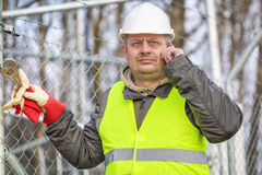 Worker with cell phone and adjustable wrench at outdoors. Winter day Stock Image