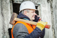 Worker with cell phone and sledge hammer near building Royalty Free Stock Images