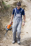 Worker with chainsaw. A worker walking with a chainsaw in his hand. A new house construction site royalty free stock photos