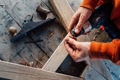 Worker changes a drill in a screwdriver, against the background of a wooden table stock images