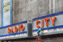 Worker changing advertising of Radio City Music Hall, an entertainment venue located in Rockefeller Stock Photo