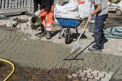 Worker is changing the pavement tiles. Stock Image
