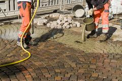 Worker is changing the pavement tiles. Stock Photo