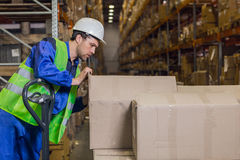 Worker checking boxes with merchandise in warehouse Royalty Free Stock Photo