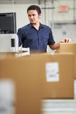 Worker Checking Goods On Belt In Distribution Warehouse Royalty Free Stock Photography
