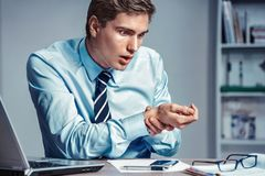 Worker checking his heart rate pulse. Photo of man working in the office. Medical concept stock image