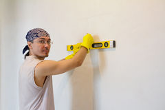 Worker checking level of house wall Stock Photo